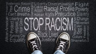 Stop Racism written on black top with sneakers in image