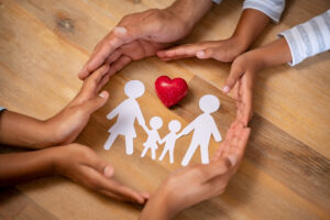 Multi-cultural hands surrounding paper cutout of family with a heart