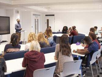 University students study in a classroom with African American male lecturer