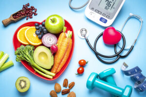 Healthy lifestyle concepts: red heart shape plate with fresh organic fruits and vegetables shot on blue background. A digital blood pressure monitor, doctor stethoscope, dumbbells and tape measure are beside the plate  This type of foods are rich in antioxidants and flavonoids that prevents heart diseases, lower cholesterol and help to keep a well balanced diet.