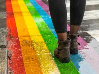 Female legs walking on rainbow crosswalk in pride parade.