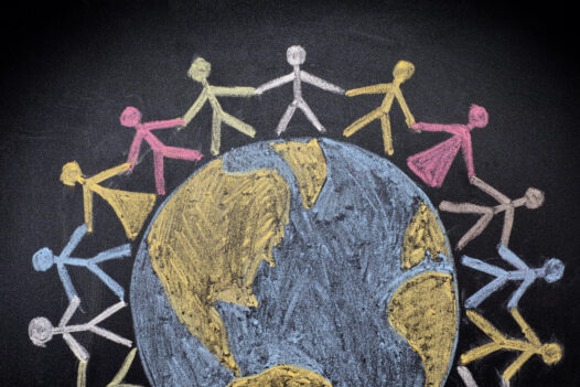 Chalk drawing of stick figures encircling the world.