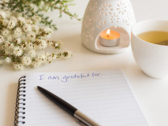 """Close up of handwritten text """"I am grateful for..."""" in foreground with notebook, pen, cup of tea, flowers and oil burner in soft focus"""
