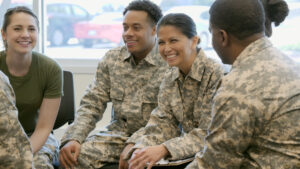 Male and female army soldiers sitting in a circle smiling and talking.