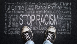 Person standing over Stop Racism word cloud.