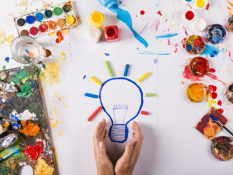 Hand drawn lightbulb with colorful paints over white paper.
