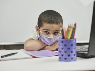 Young stressed out student wearing a mask staring at a laptop
